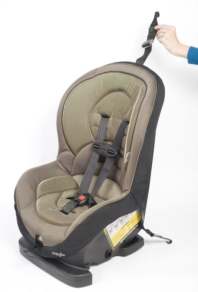 A hand holds up the tether strap on a car seat