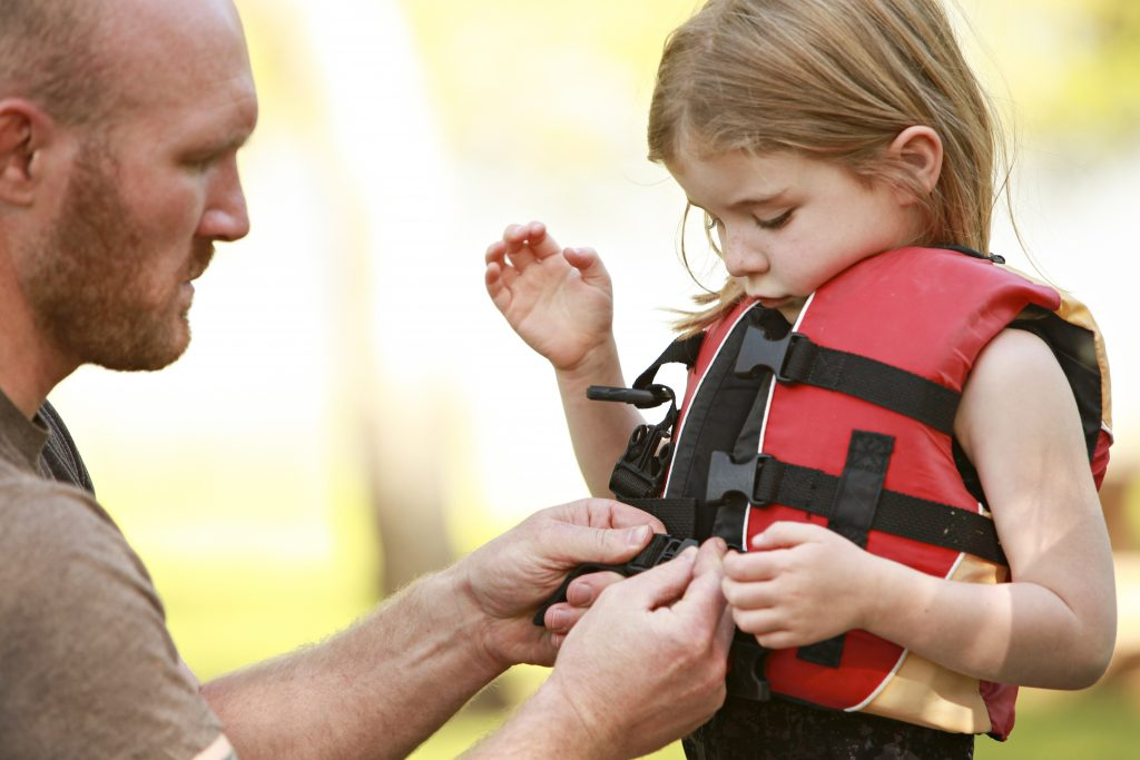A man helps a young girl clip on her personal flotation device (PFD)/lifejacket