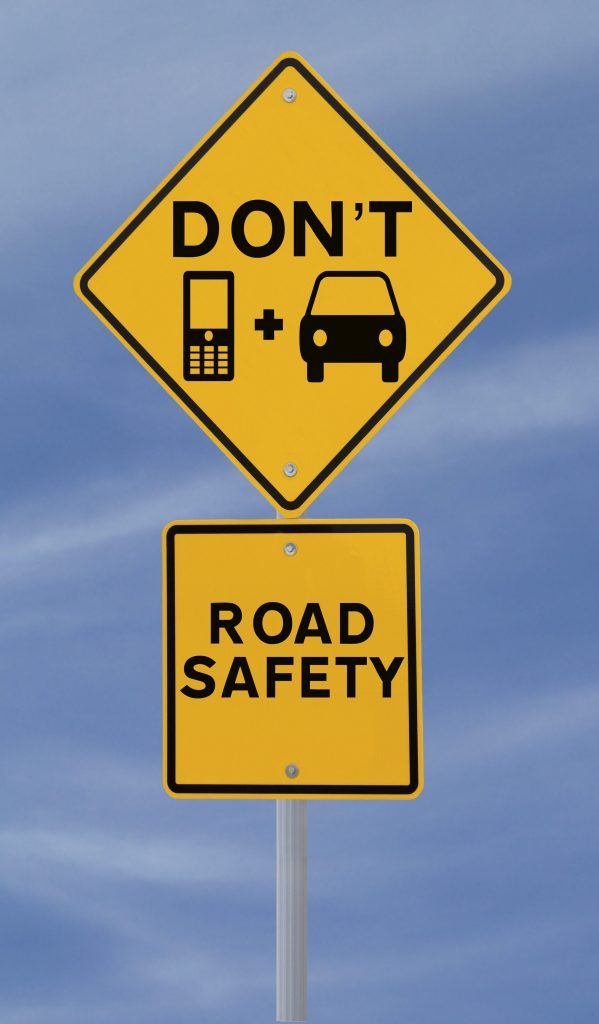 Two yellow signs stating don't text and drive; road safety in black lettering