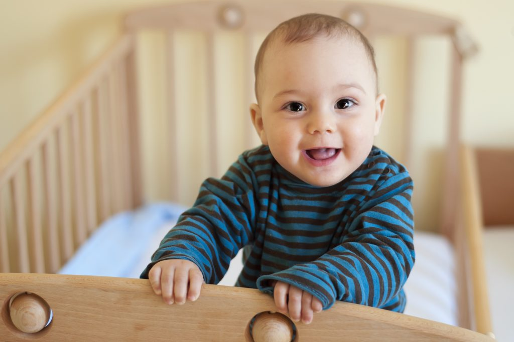 Close-up of a baby smiling and standing in a crib