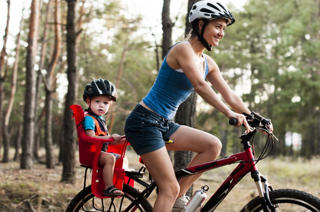 Woman riding bike with child in bike carrier